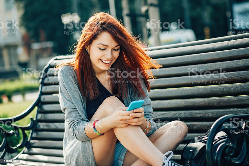 Teenage girl checking messages outdoors stock photo