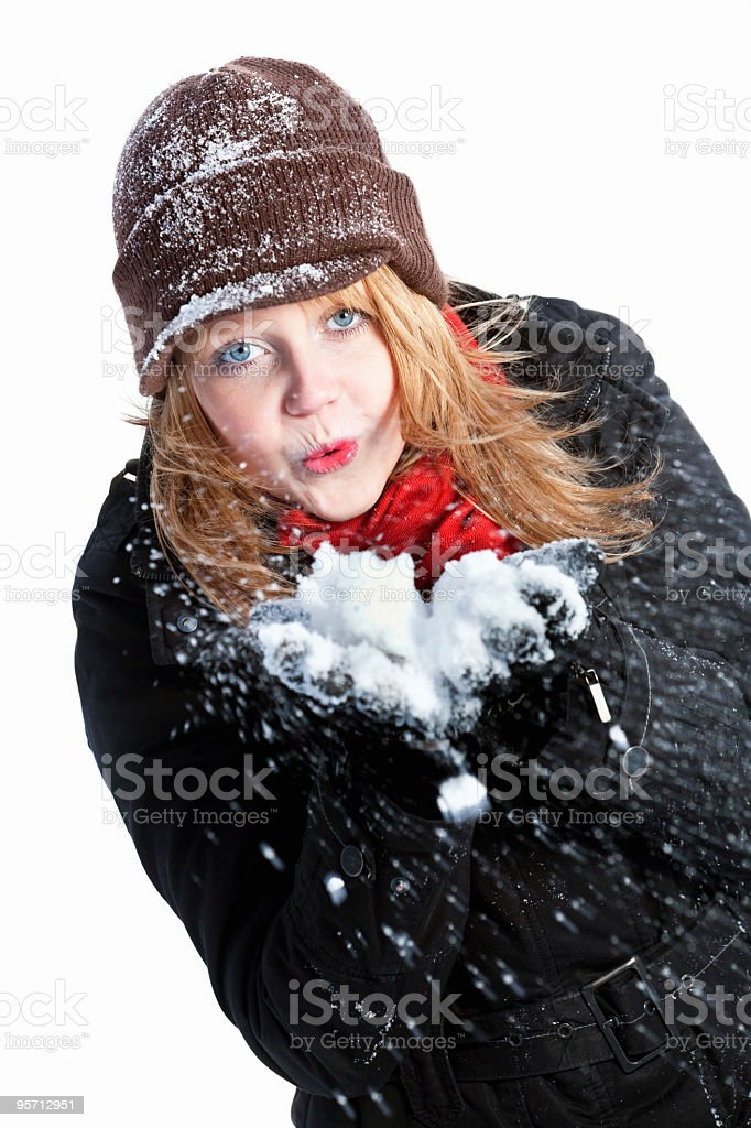 Teenage girl cheerfully blowing into snow in her hand stock photo