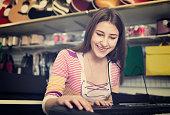Teenage girl choosing synthesizer
