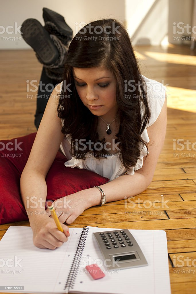 Teenage Girl Doing Her Homework on the Floor royalty-free stock photo