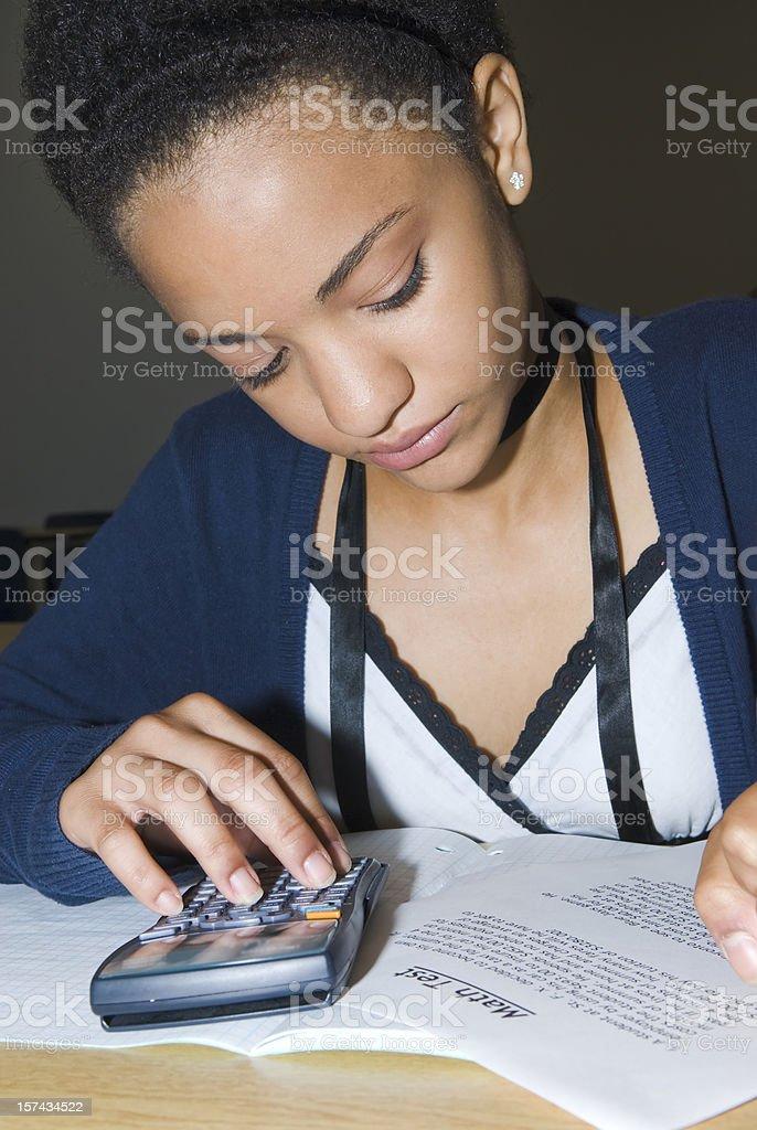 Teenage girl doing math test - I royalty-free stock photo