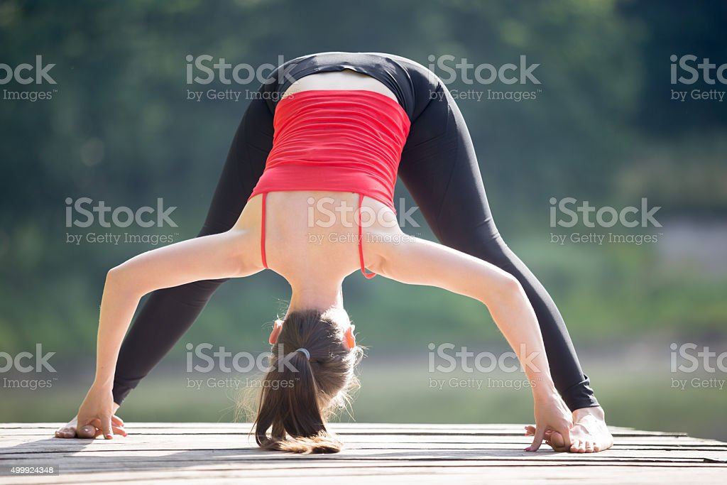Teenage girl doing Standing Straddle Forward Bend stock photo