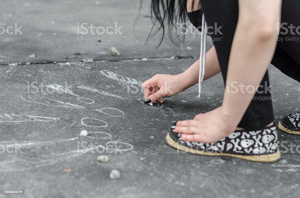 Teenage girl draws on the floor with chalk signs stock photo