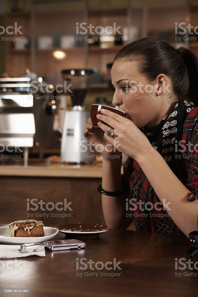 Teenage girl (15-17) drinking cup of coffee in cafe, side view stock photo
