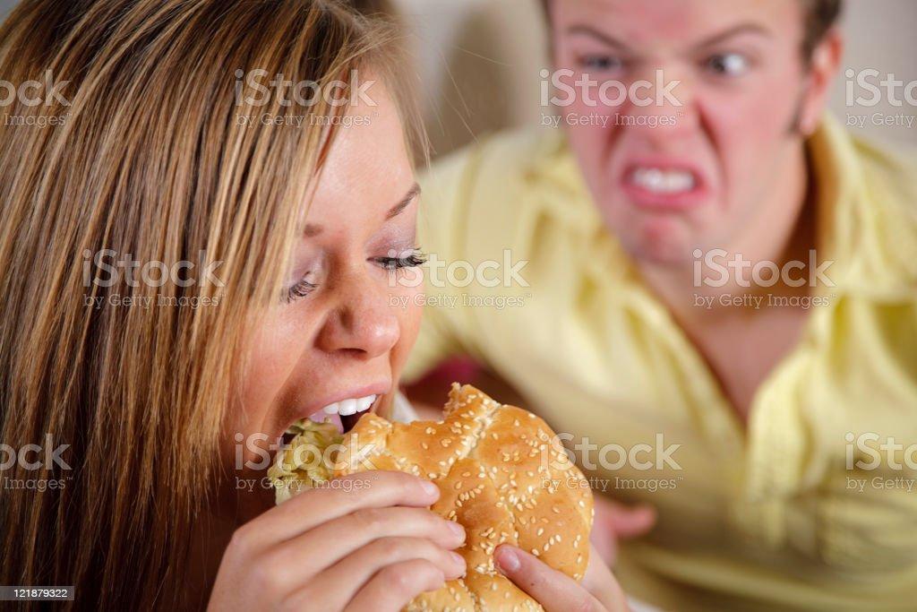 Teenage Girl Eating a Cheeseburger royalty-free stock photo