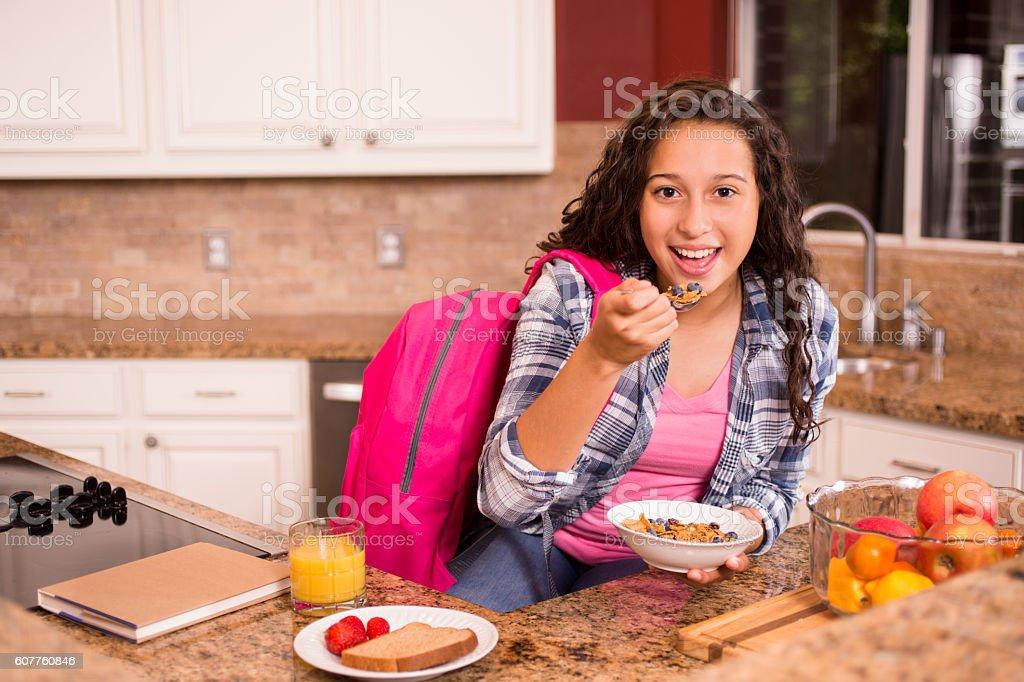 Teenage girl eating breakfast before going to school. stock photo
