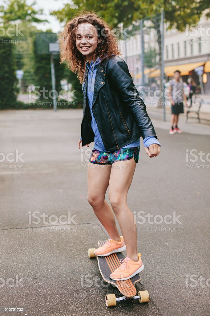 Teenage girl enjoying skating outdoors stock photo