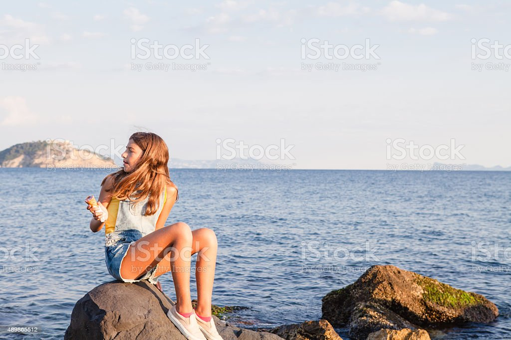 Teenage girl enjoys icecream at seaside stock photo