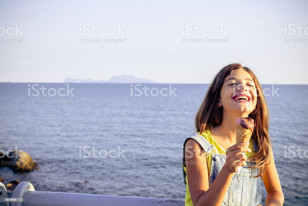 Teenage girl enjoys icecream at seaside stock photo