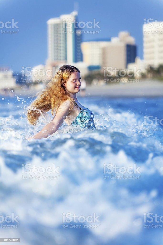 Teenage Girl Enjoys Wave Near Beach with Foaming CopySpace royalty-free stock photo