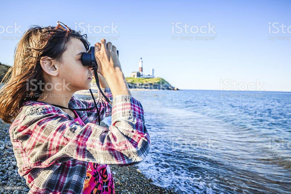 Teenage girl exploring ocean with binocular royalty-free stock photo