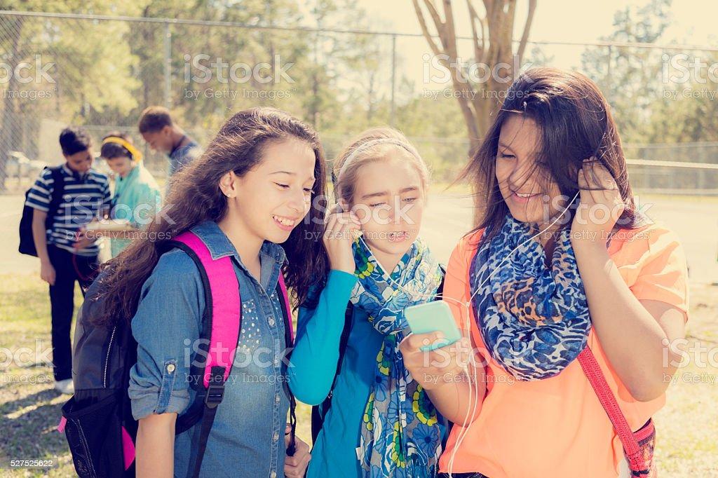 Teenage girl friends listen to music on smart phone.  Park. stock photo