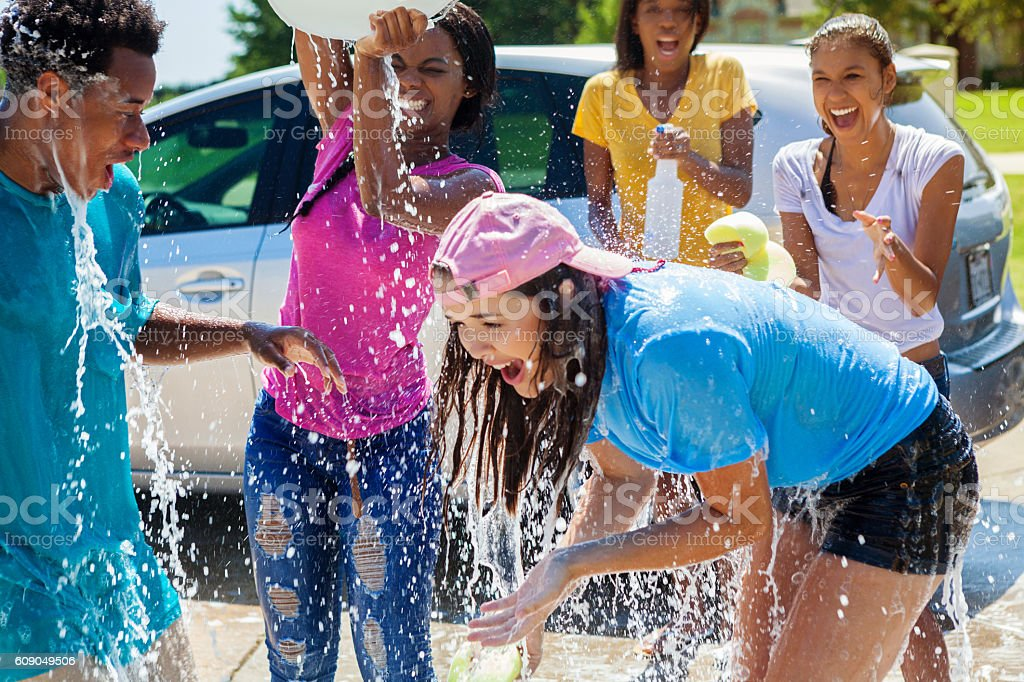 Teenage girl gets soaked during car wash stock photo