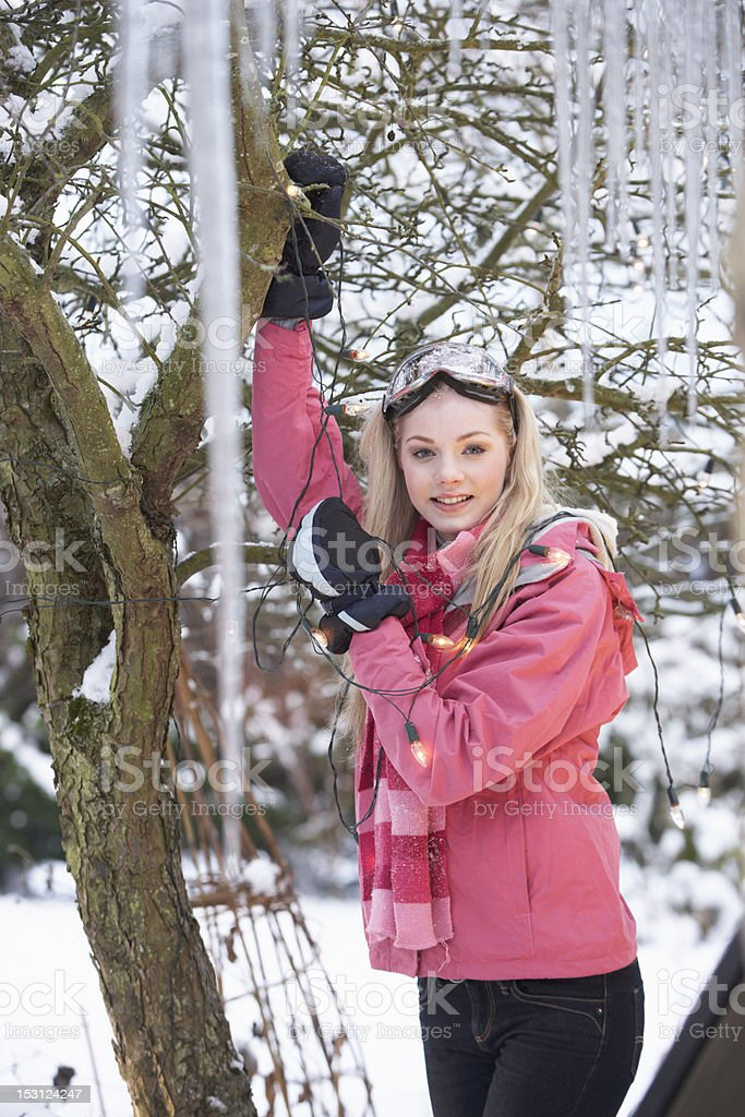 Teenage Girl Hanging Fairy Lights In Tree With Icicles stock photo