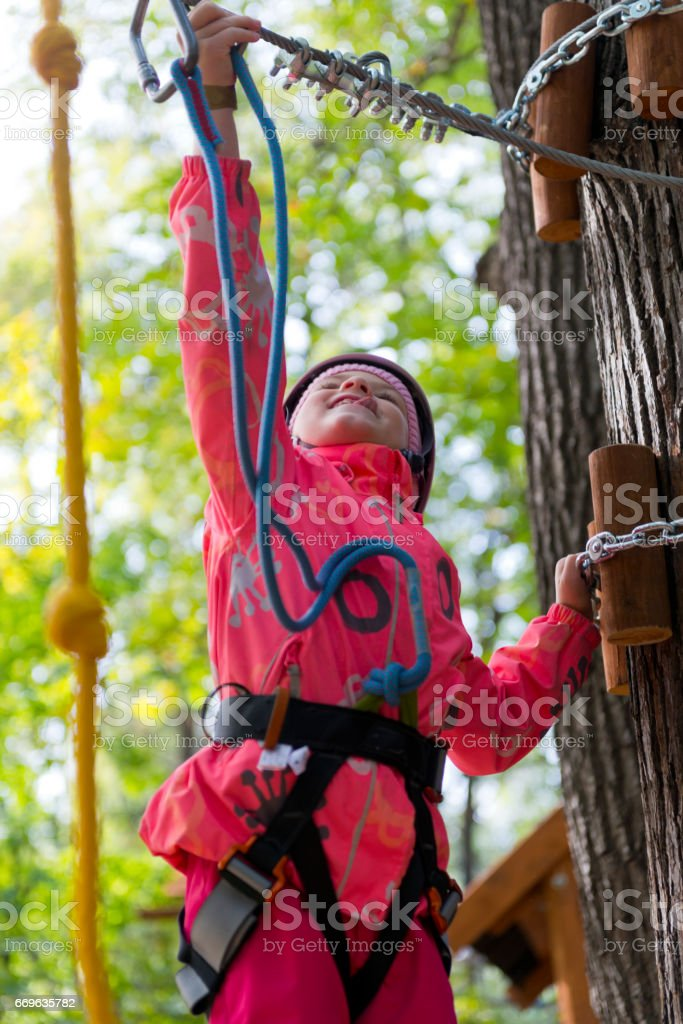 Teenage girl having fun in ropes course adventure park. Zipline for Kids. stock photo