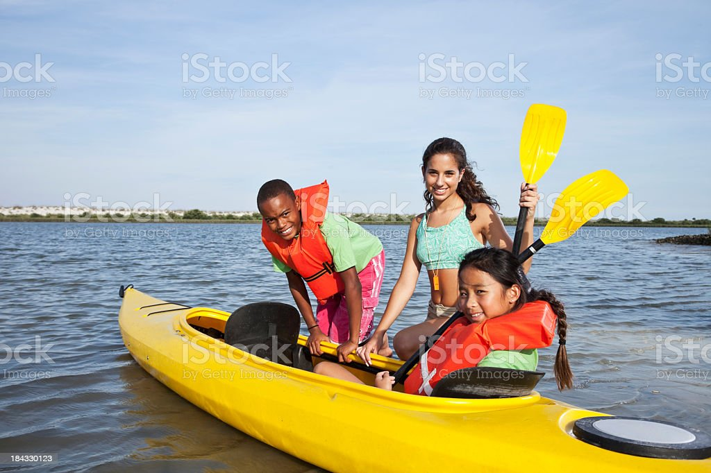 Teenage girl helping children with kayak stock photo