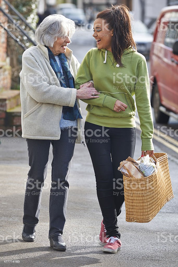 Teenage Girl Helping Senior Woman To Carry Shopping royalty-free stock photo