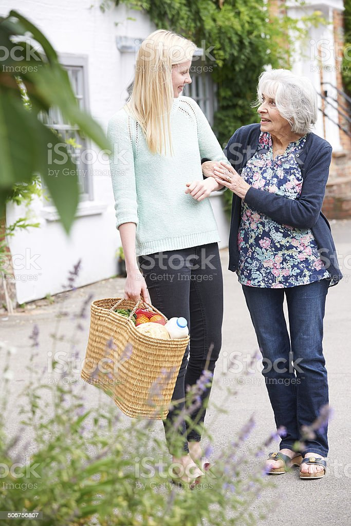 Teenage Girl Helping Senior Woman To Carry Shopping stock photo