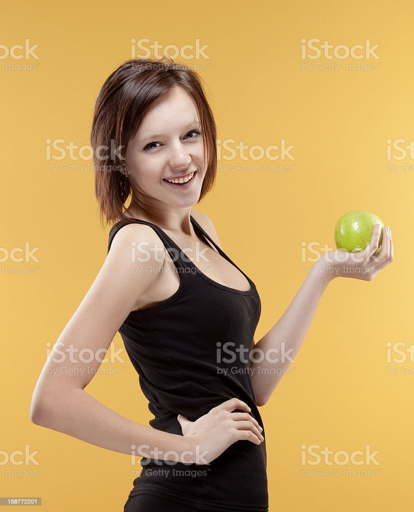 teenage girl holding a green apple smiling royalty-free stock photo