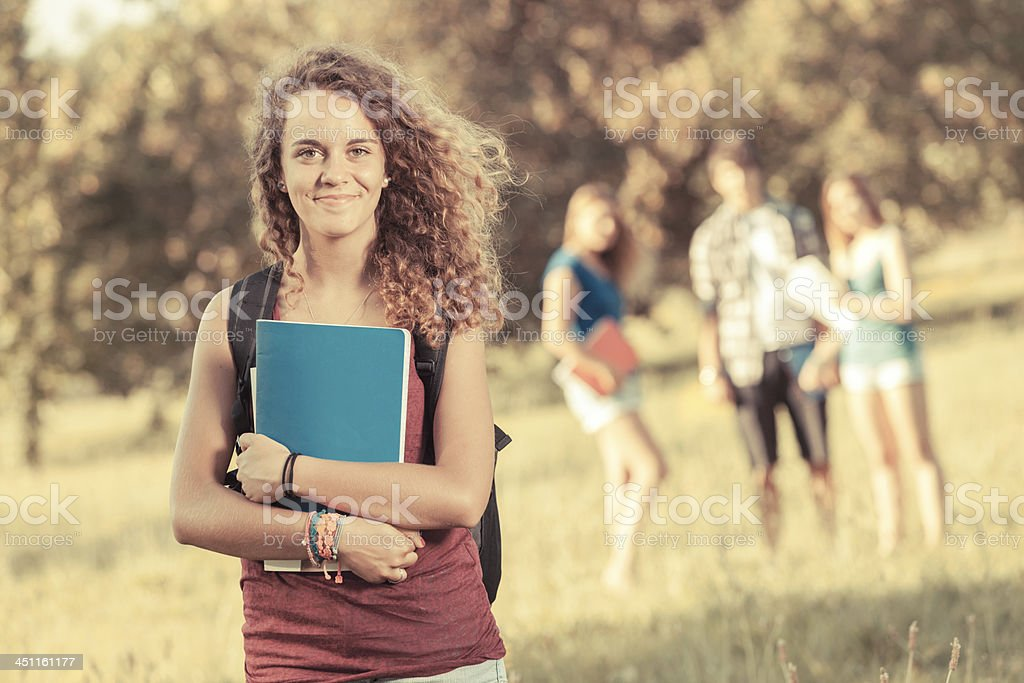 A teenage girl holding books in a park stock photo