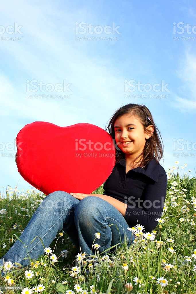Teenage girl holding red heartshape in nature royalty-free stock photo