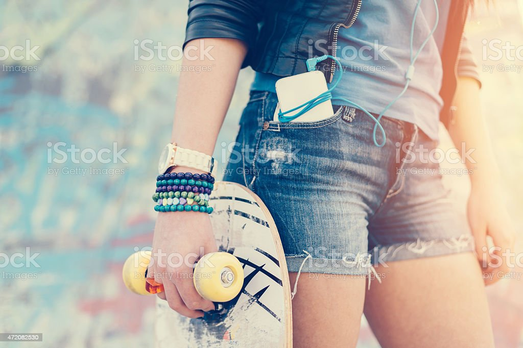 Teenage girl holding skateboard stock photo