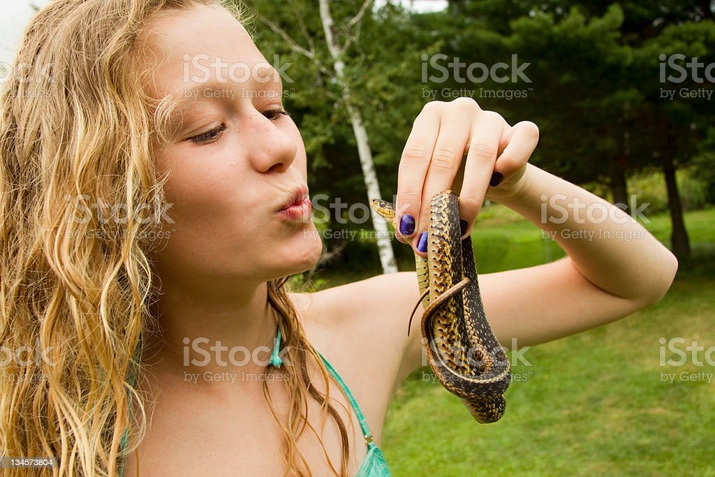 Teenage girl holding small snake stock photo