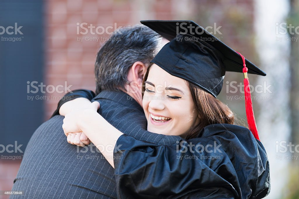Teenage girl hugging father wearing graduation gown stock photo