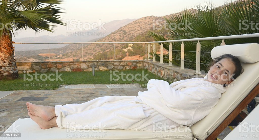 Teenage girl in a bathrobe by the pool royalty-free stock photo