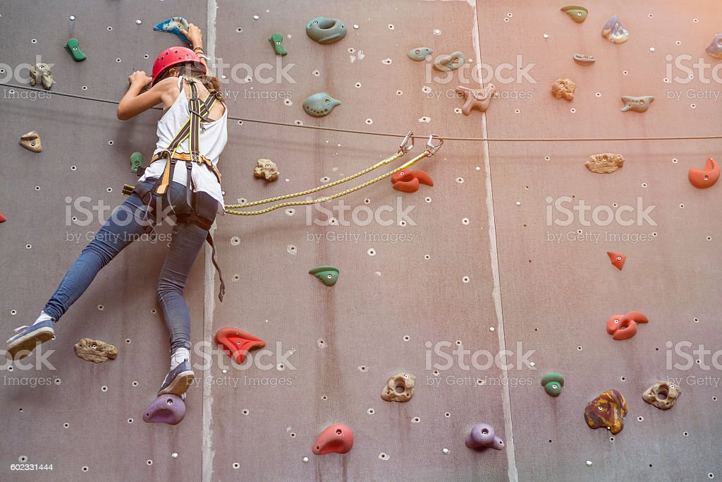 teenage girl in a free climbing wall stock photo