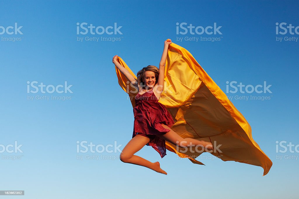 Teenage girl in ballet dress jumping with flying yellow fabric stock photo