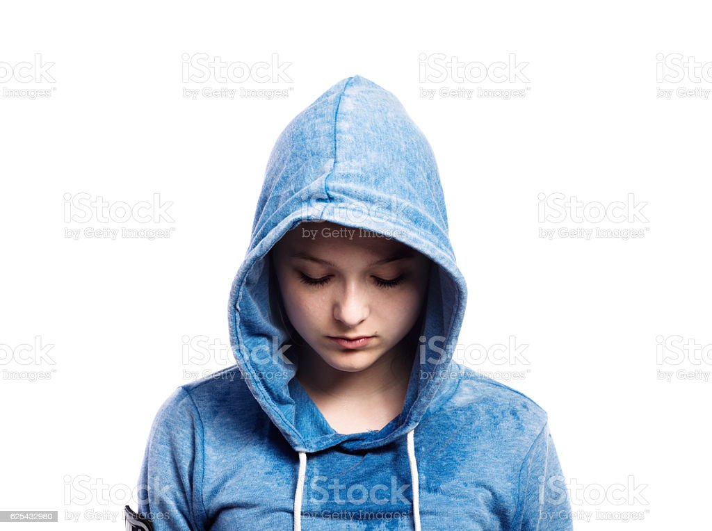 Teenage girl in blue sweatshirt. Studio shot, isolated. stock photo