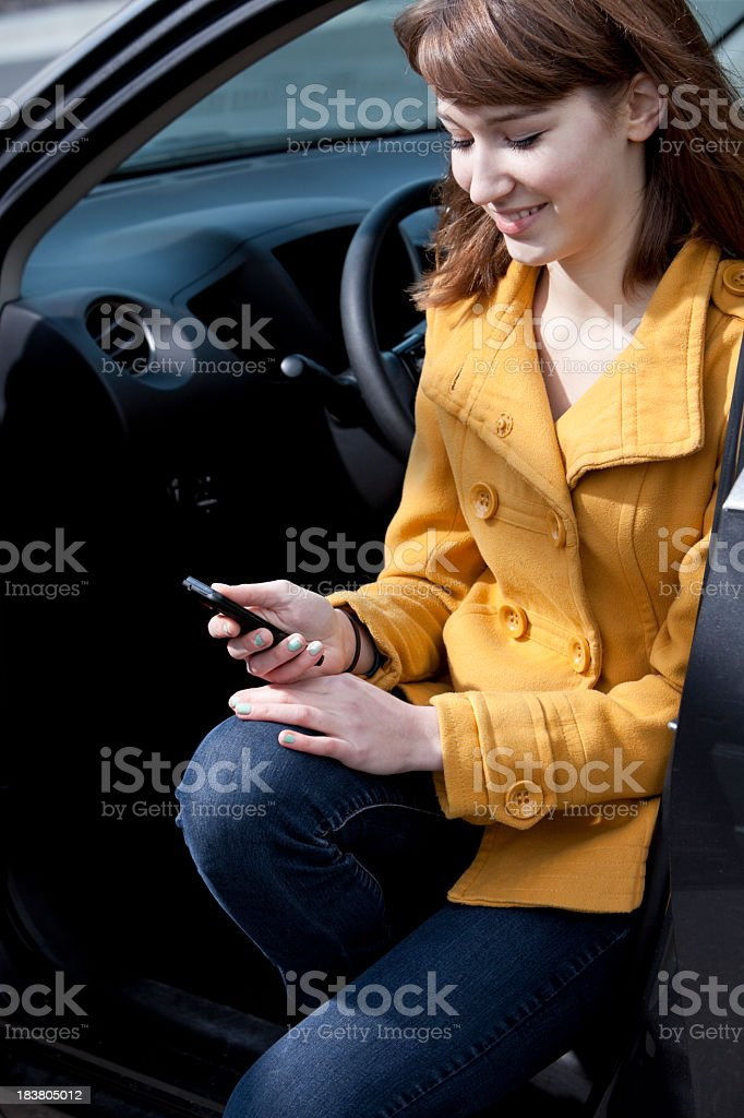 Teenage girl in car with mobile phone stock photo