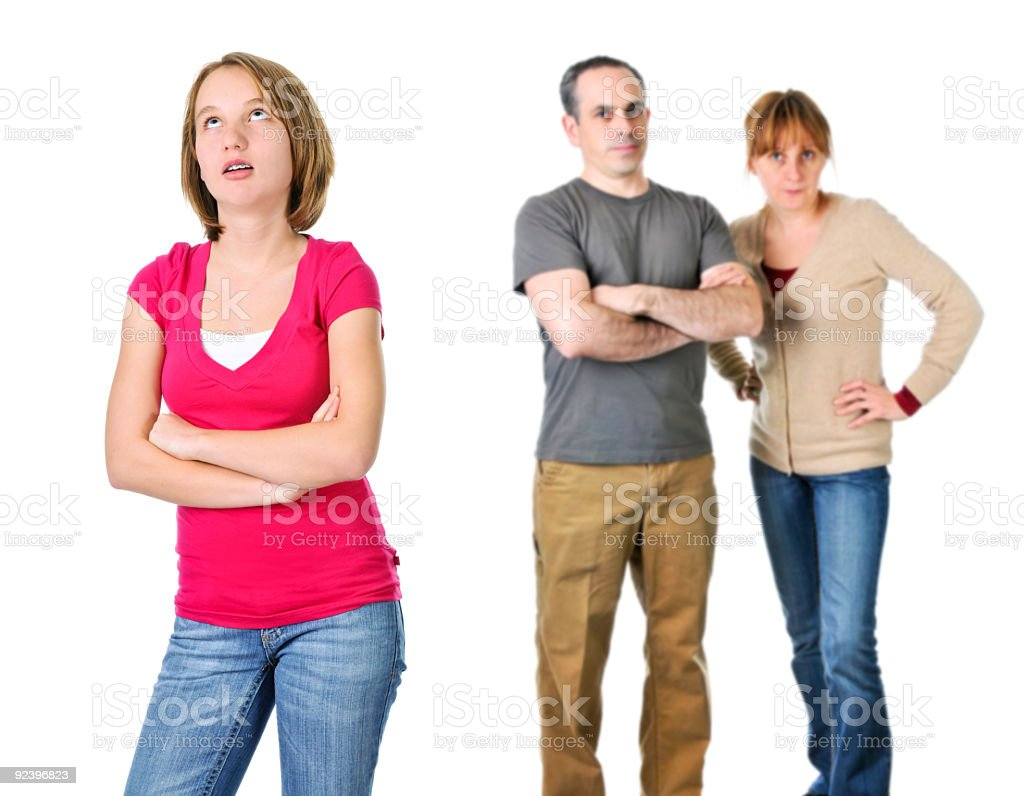 Teenage girl in foreground looking exasperated with parents royalty-free stock photo