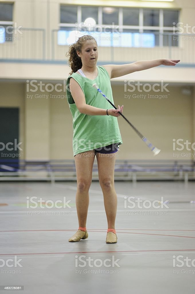 Teenage girl in gym twirling baton stock photo
