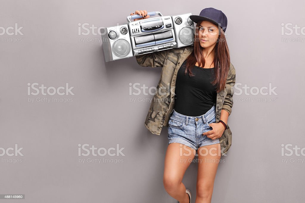 Teenage girl in hip hop clothes holding a ghetto blaster stock photo