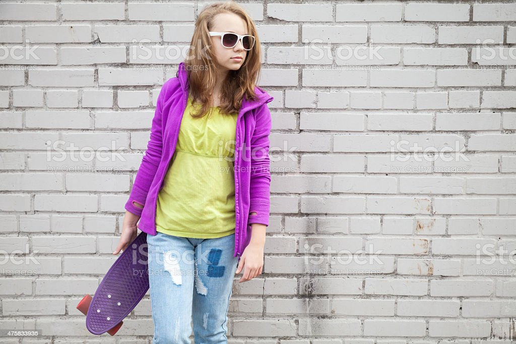 Teenage girl in jeans and sunglasses with skateboard stock photo