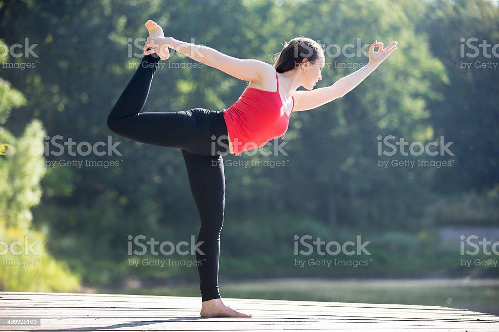 Teenage girl in Natarajasana pose stock photo