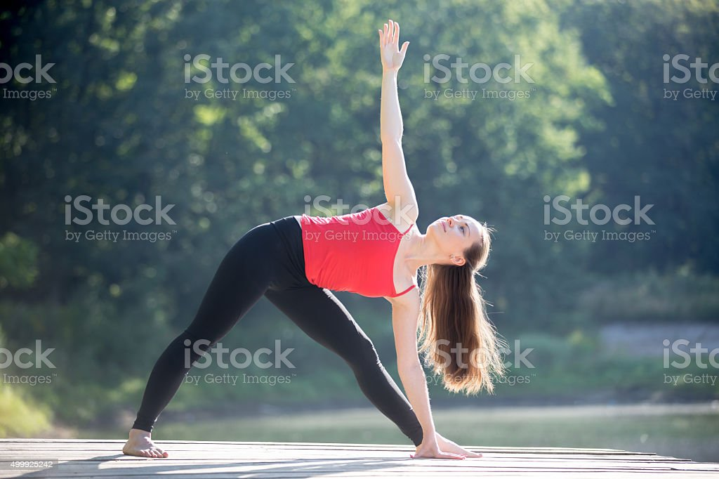 Teenage girl in Utthita Trikonasana Pose stock photo