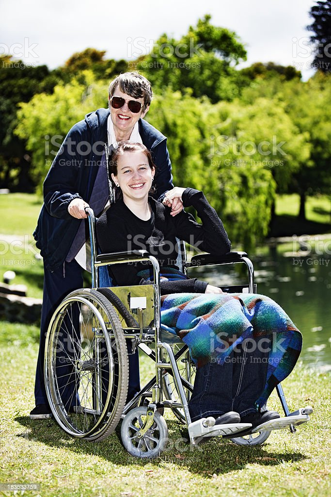 Teenage girl in wheelchair with elderly carer hold hands, smile royalty-free stock photo