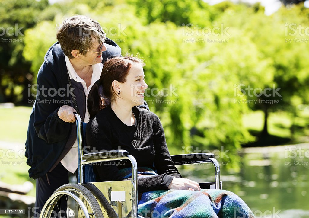 Teenage girl in wheelchair with elderly carer smiles by lake royalty-free stock photo