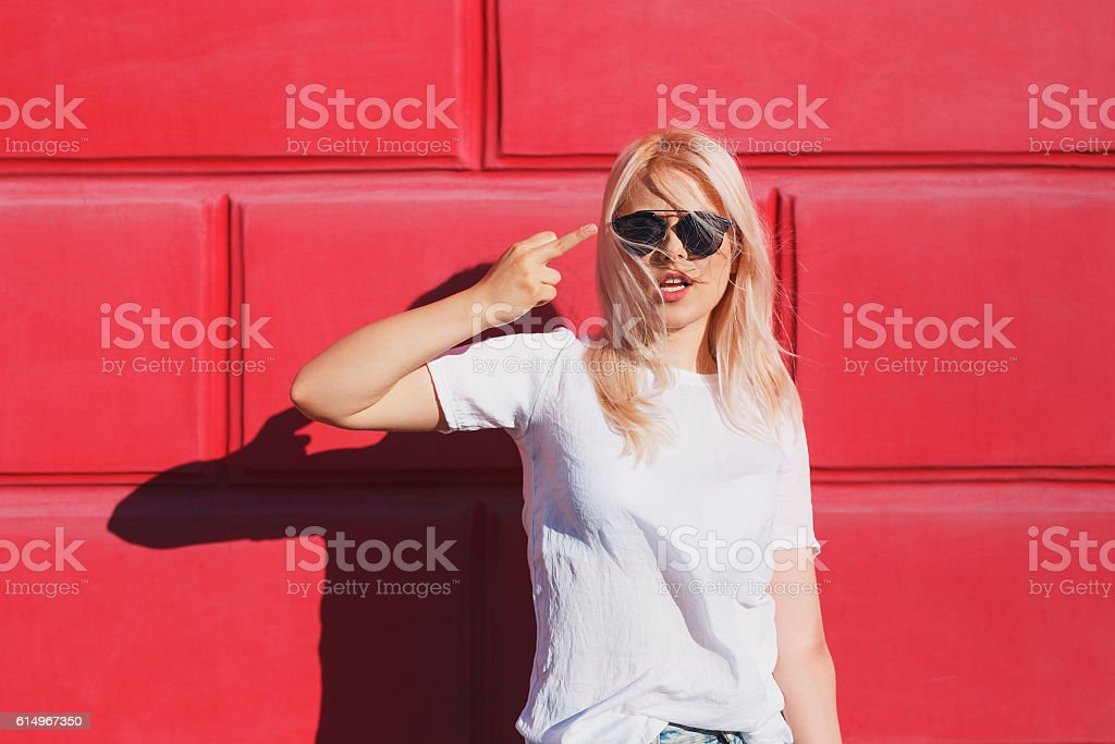 teenage girl in white t-shirt and shades showing middle stock photo