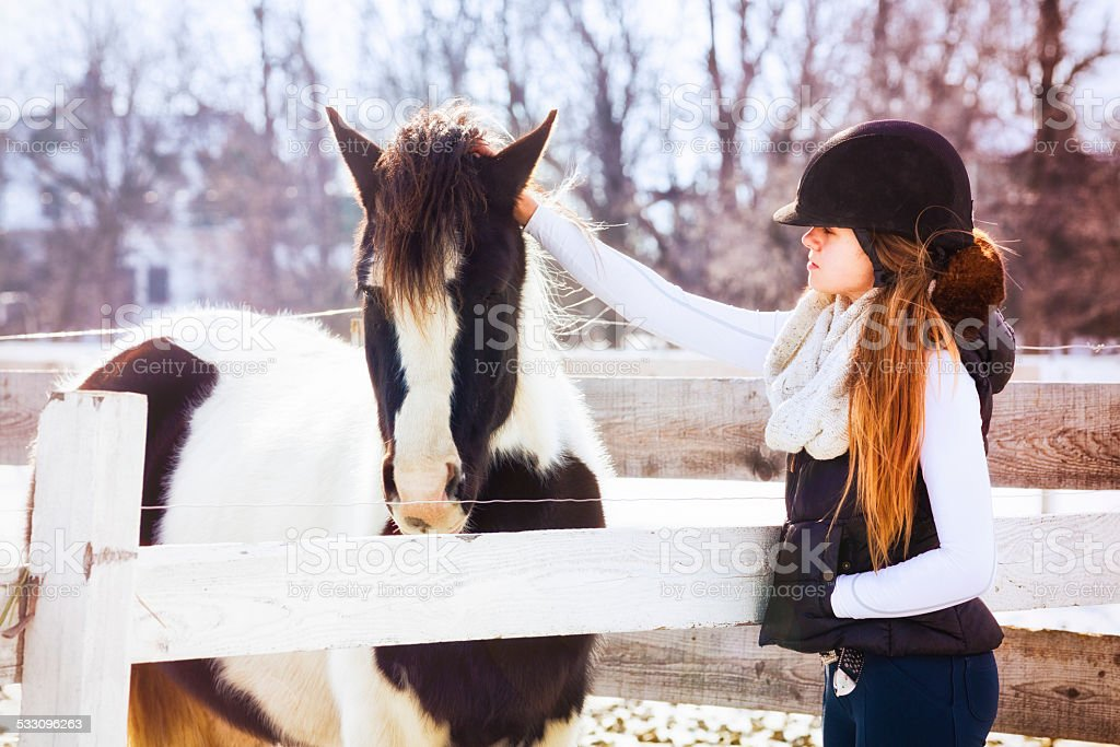 Teenage girl in winter riding gear stroking a pony stock photo