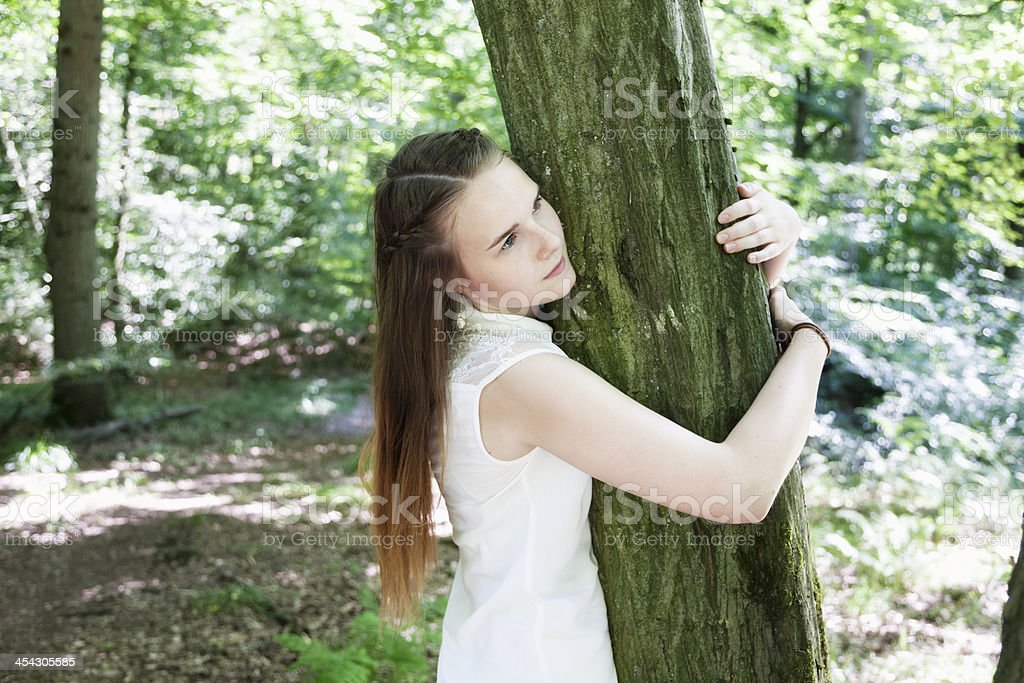 teenage girl in woods embracing tree stock photo