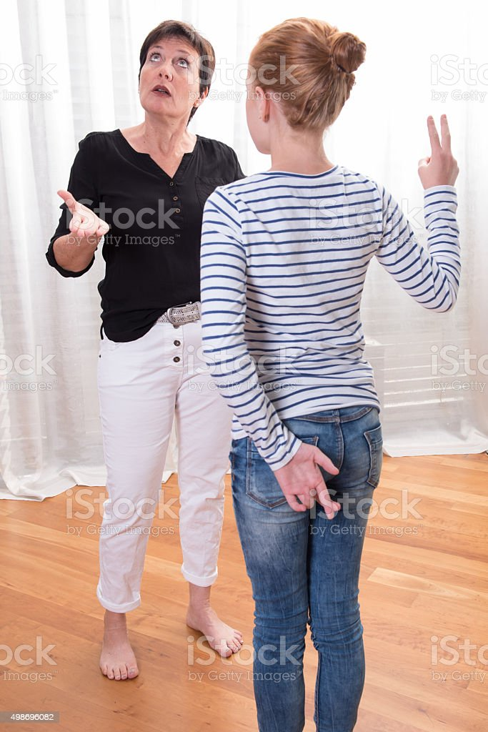 teenage girl is cheating - mother looks angry stock photo