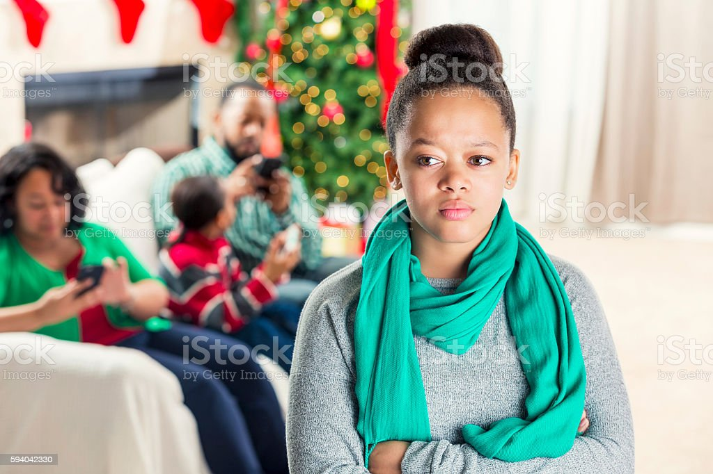 Teenage girl is ignored by family at Christmastime stock photo