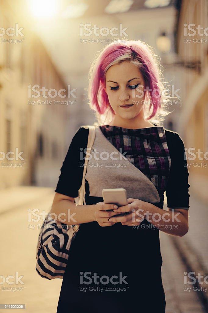 Teenage girl is using her smart phone stock photo