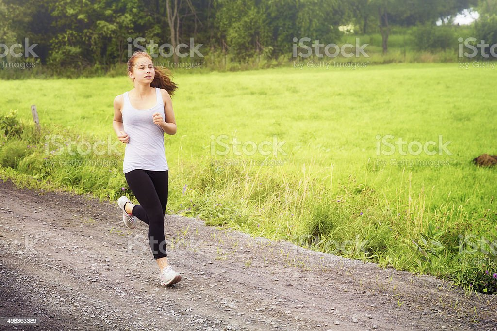 Teenage girl jogging on rural road royalty-free stock photo
