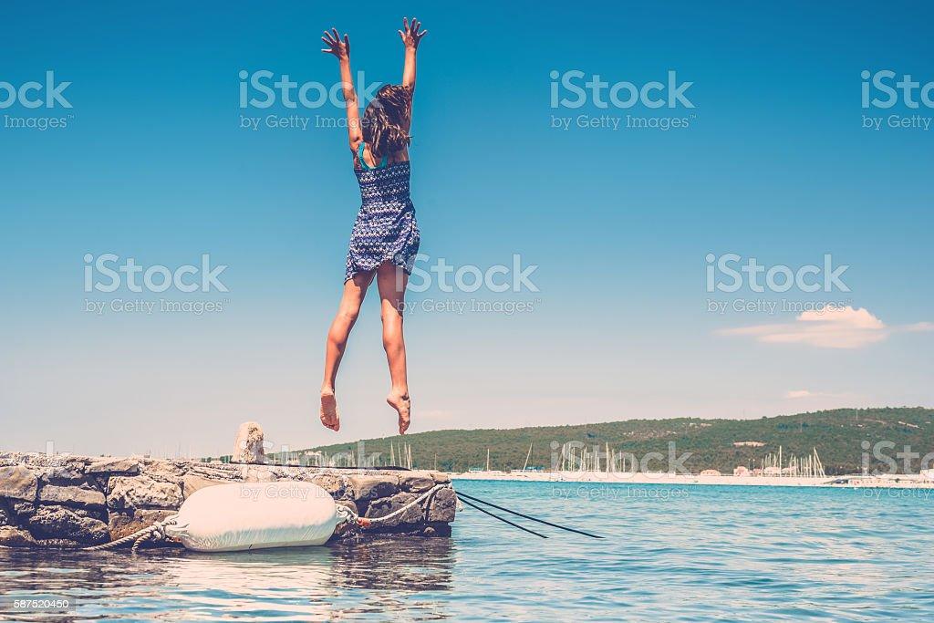 teenage girl jumping high at croatian coast stock photo
