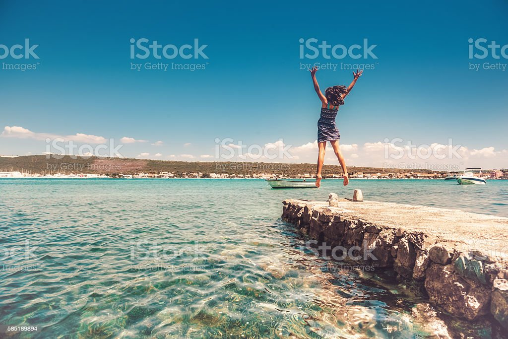 teenage girl jumping high on landing stage at croatian coast stock photo